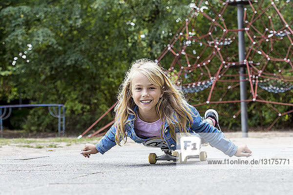 Portrait of smiling blond girl with skateboard on a playground