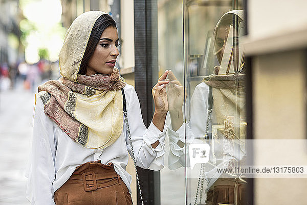 Spanien  Granada  junge muslimische Touristin im Hidschab  die auf Schaufenster in einer Einkaufsstraße schaut