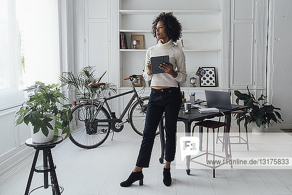 Mid adult freelancer standing in her home office  using digital tablet