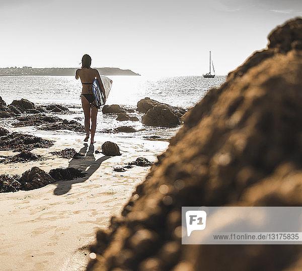 Frankreich  Bretagne  junge Frau trägt Surfbrett an einem felsigen Strand am Meer
