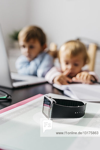 Smartwatch on a desk  with children using laptop in the background