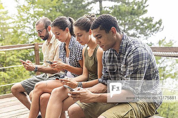 Italien  Massa  Wanderer in den Alpi Apuane  die auf ihre Smartphones schauen und auf einer Bank sitzen
