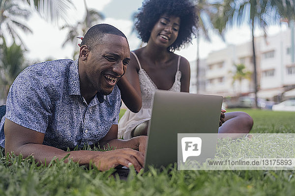 USA  Florida  Miami Beach  laughing young couple looking at laptop on lawn in a park