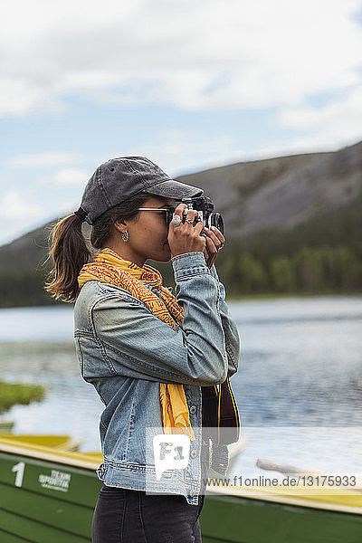 Finland,  Lapland,  woman taking picture with a camera at the lakeside