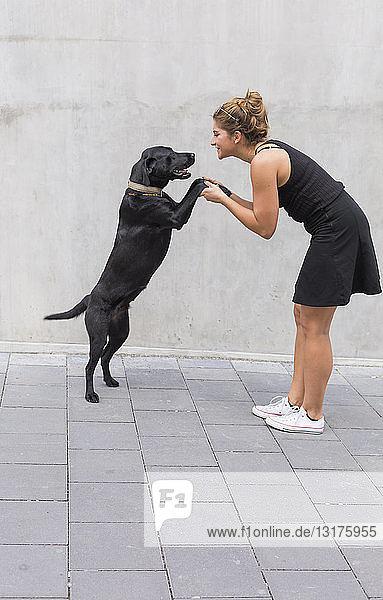 Junge Frau in Schwarz gekleidet mit ihrem schwarzen Hund
