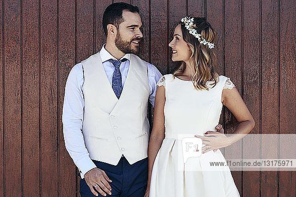 Brautpaar steht vor der Strandhütte und sieht sich an