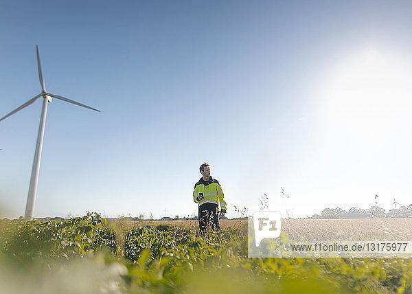 Ingenieur  der auf einem Feld eines Windparks steht