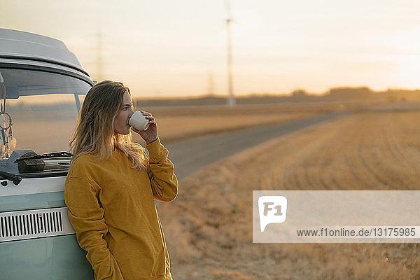 Junge Frau trinkt bei Sonnenuntergang aus Becher am Wohnmobil in ländlicher Landschaft