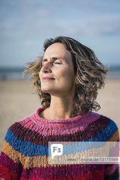 Reife Frau genießt den Wind am Strand  Porträt