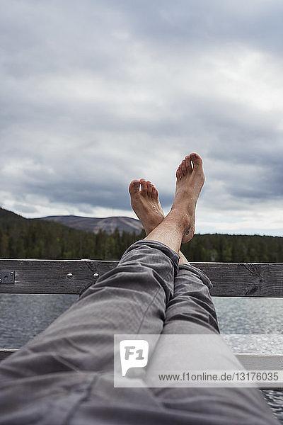 Mann sitzt auf einem Steg an einem See und hält die Füße hoch