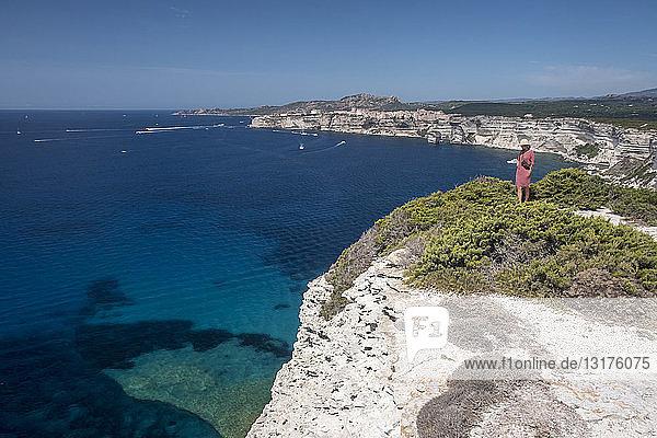 Korsika  Mittelmeerküste  Frau auf Felsklippe stehend