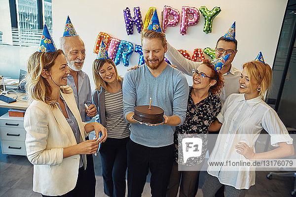 Kollegen mit einer Geburtstagsfeier im Büro mit Kuchen und Partyhüten
