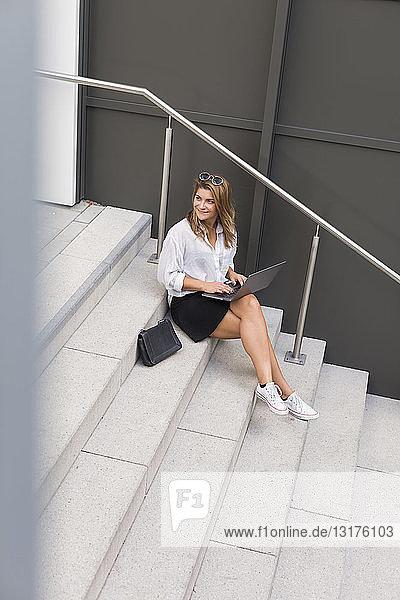 Lächelnde Geschäftsfrau sitzt mit Laptop auf der Treppe