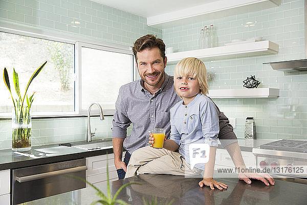 Porträt eines Jungen mit Vater in der Küche mit einem Glas Orangensaft