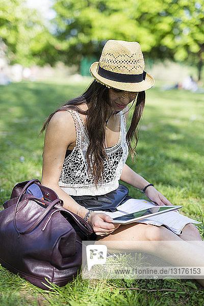 Junge Studentin sitzt auf einer Wiese in einem Park und benutzt ein digitales Tablett