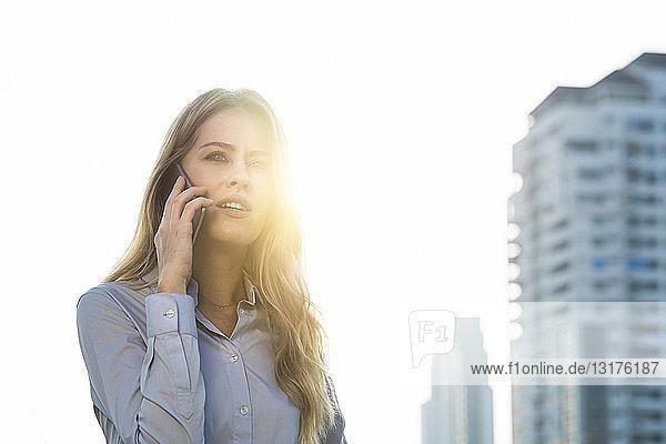 Geschäftsfrau spricht auf dem Dach der Stadt in ein Smartphone