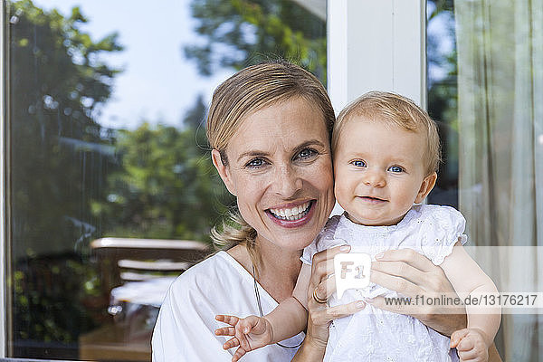 Portrait of happy mother holding her baby girl at the window