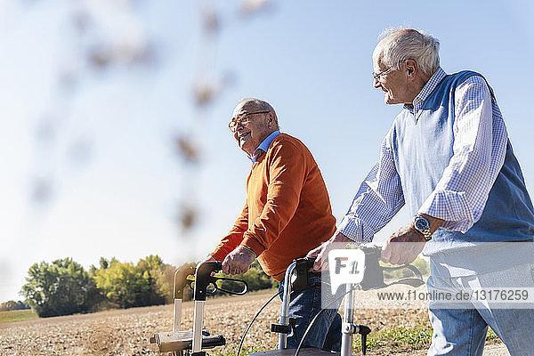 Zwei alte Freunde gehen auf einer Landstraße und benutzen Rollatoren