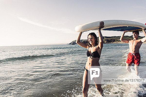 Frankreich  Bretagne  glückliches junges Paar mit einem SUP-Board gemeinsam auf dem Meer
