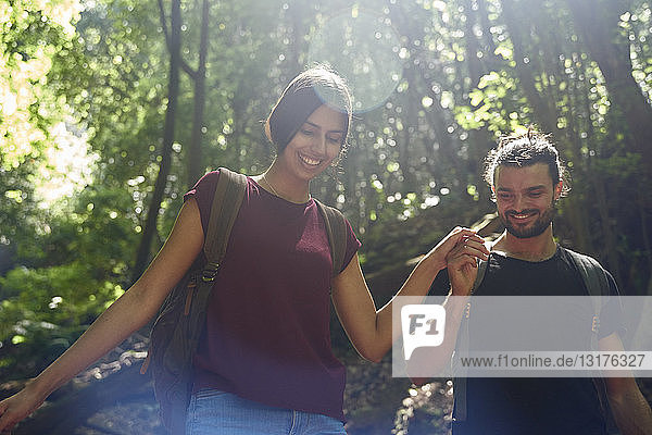 Spanien  Kanarische Inseln  La Palma  lächelndes Paar geht Hand in Hand durch einen Wald