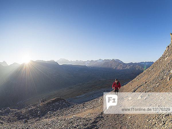 Border region Italy Switzerland  senior man hiking in mountain landscape at Piz Umbrail