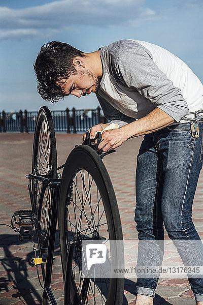 Junger Mann repariert Pendler-Fixie-Fahrrad