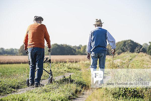 Alte Freunde machen einen Feldspaziergang mit Spazierstock und Rollator und sprechen über alte Zeiten