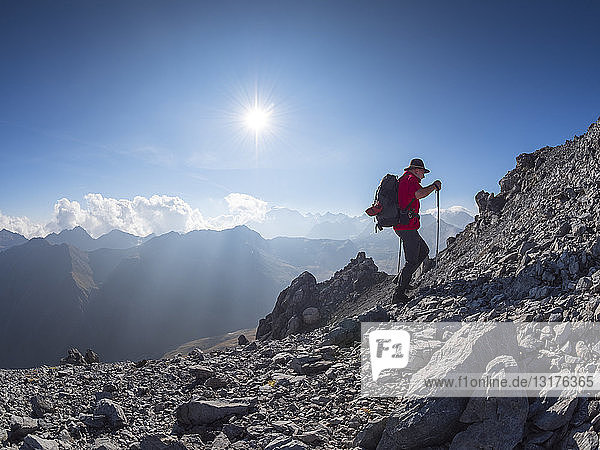 Border region Italy Switzerland  senior man hiking in mountain landscape at Piz Umbrail