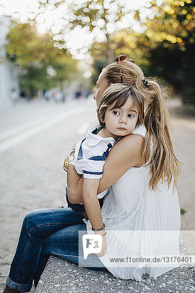 Mother sitting on bench  embracing her son