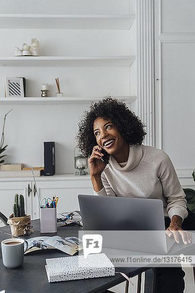 Mittlere erwachsene Frau  die in ihrem Heimbüro arbeitet und ein Smartphone benutzt
