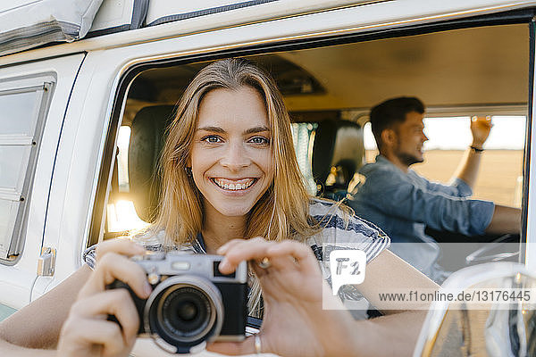 Portrait of happy woman with camera leaning out of window of a camper van with man driving