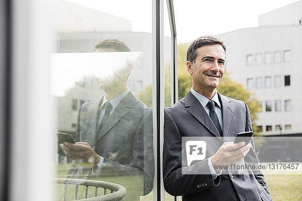 Lächelnder Geschäftsmann mit an die Glasfront gelehntem Handy