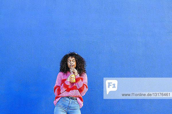 Porträt einer jungen Frau mit Flasche Orangensaft vor blauer Wand stehend