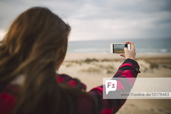 Back view of young woman taking picture with smartphone on the beach