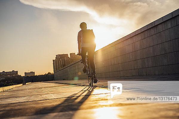 Junger Mann mit Rucksack fährt Fahrrad auf der Promenade bei Sonnenuntergang