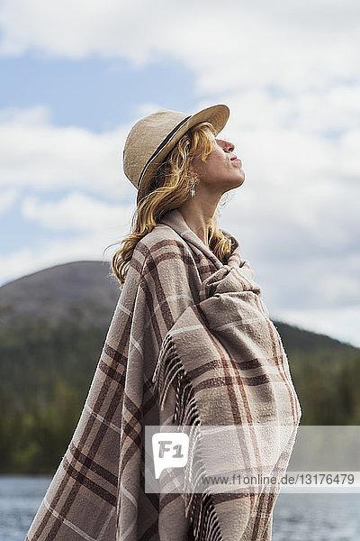 Finnland  Lappland  am Seeufer stehende Frau mit einem Hut  der in eine Decke gehüllt ist