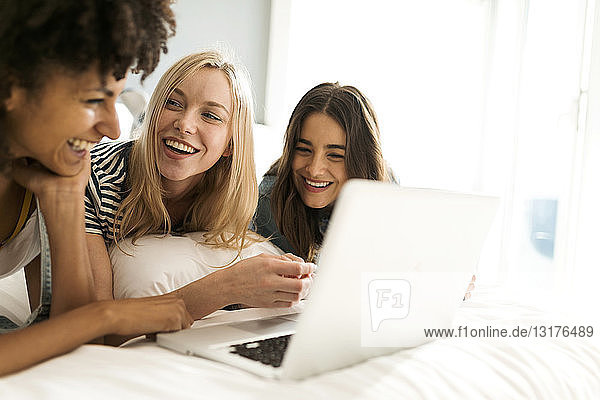Three happy girlfriends lying on bed sharing laptop