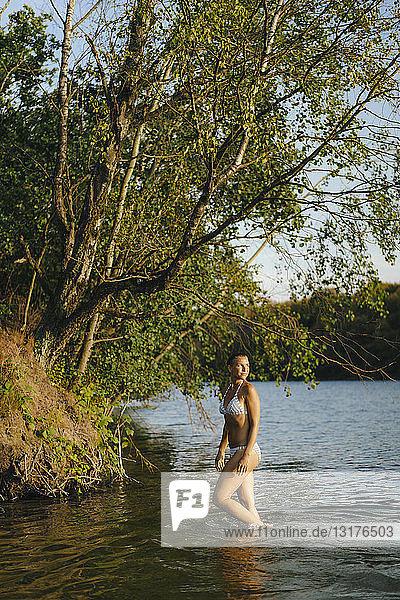 Woman wearing a bikini wading in a lake