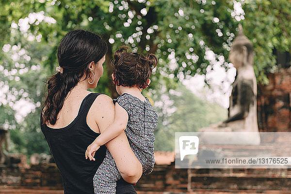 Thailand  Ayutthaya  Mutter und Tochter betrachten eine Buddha-Statue im Wat Mahathat