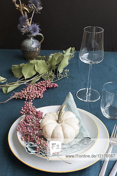 Herbstliche Tischdekoration mit weißem Zierkürbis und rosa Pfefferkörnern