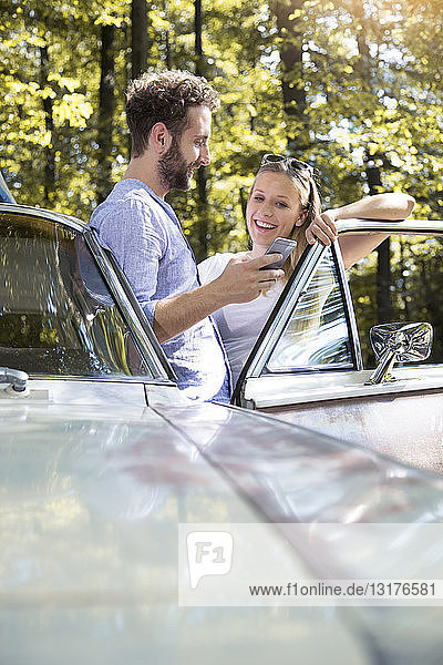 Smiling young couple with cell phone at car in forest