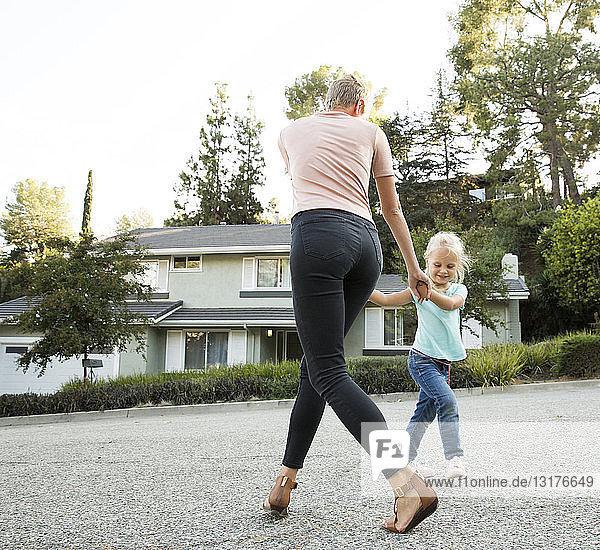 Mutter spielt mit Tochter vor ihrem Haus