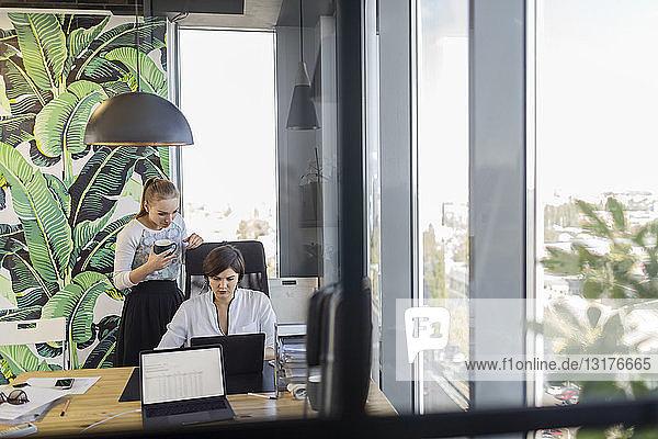 Two women at desk in office