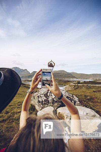 Norwegen  Lofoten  junge Frau  die eine Frau in Yoga-Pose fotografiert