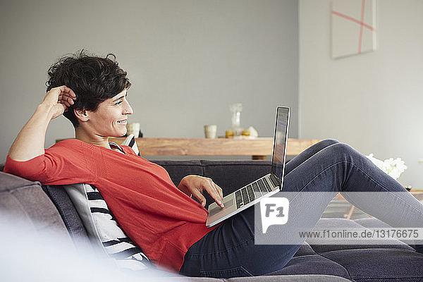 Lächelnde Frau mit Laptop auf der Couch zu Hause