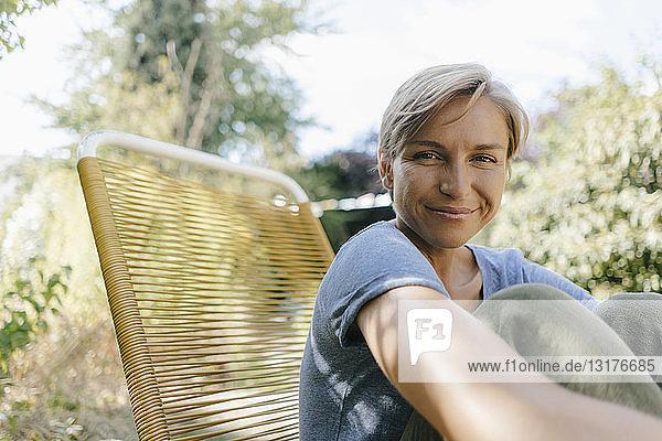 Porträt einer lächelnden Frau  die im Garten auf einem Stuhl sitzt