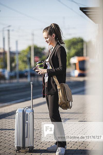 Junge Frau mit Gepäck an der Straßenbahnhaltestelle in der Stadt mit Mobiltelefon