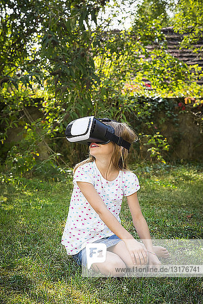 Smiling little girl wearing Virtual Reality Glasses in the garden