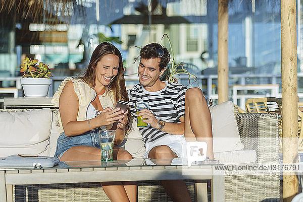 Glückliches junges Paar sitzt auf der Terrasse einer Bar und schaut auf sein Handy