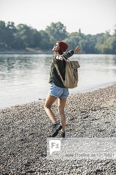 Unbeschwerte junge Frau beim Spaziergang am Flussufer